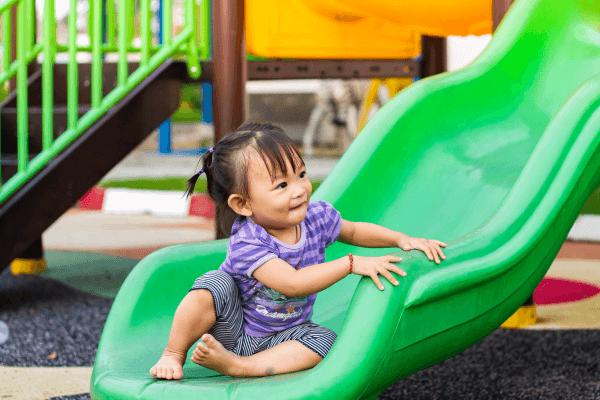 Toddler Girl at Bottom of Playground Slide